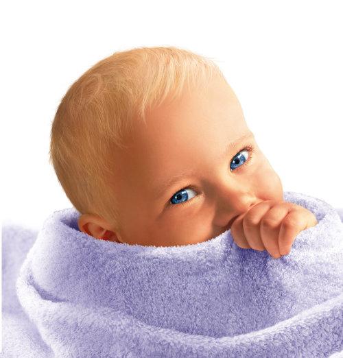 Bebé de ojos azules envuelto en una toalla