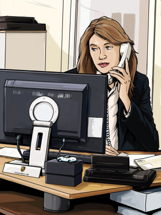 receptionist with telephone sitting in front of computer